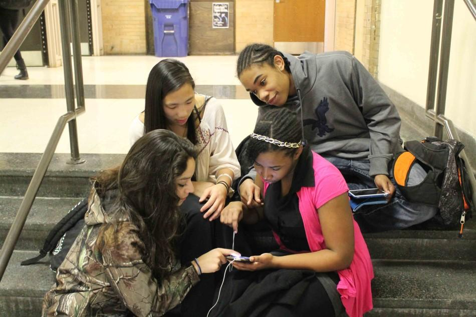Freshmen Neftali Quiroz, Meghan Ter Molen, Gariecia Rose, and Athos Zachery check Yik-Yak on their phones.