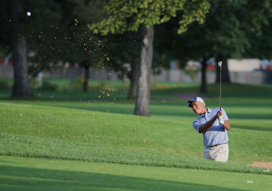 Robert James chips the ball onto the green during a game against New Trier.