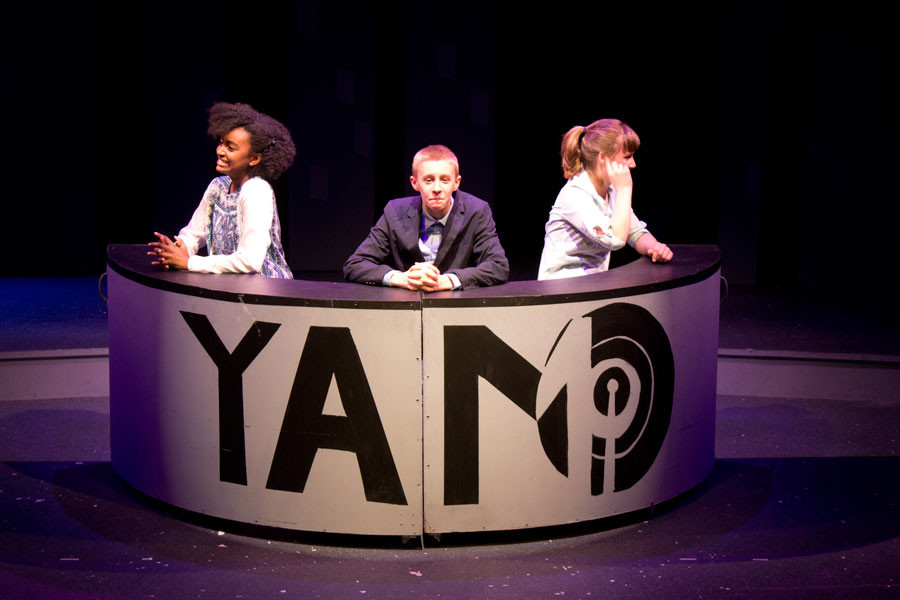 Three+performers+sit+at+a+news+ask+for+one+of+YAMO%27s+most+popular+skits.+