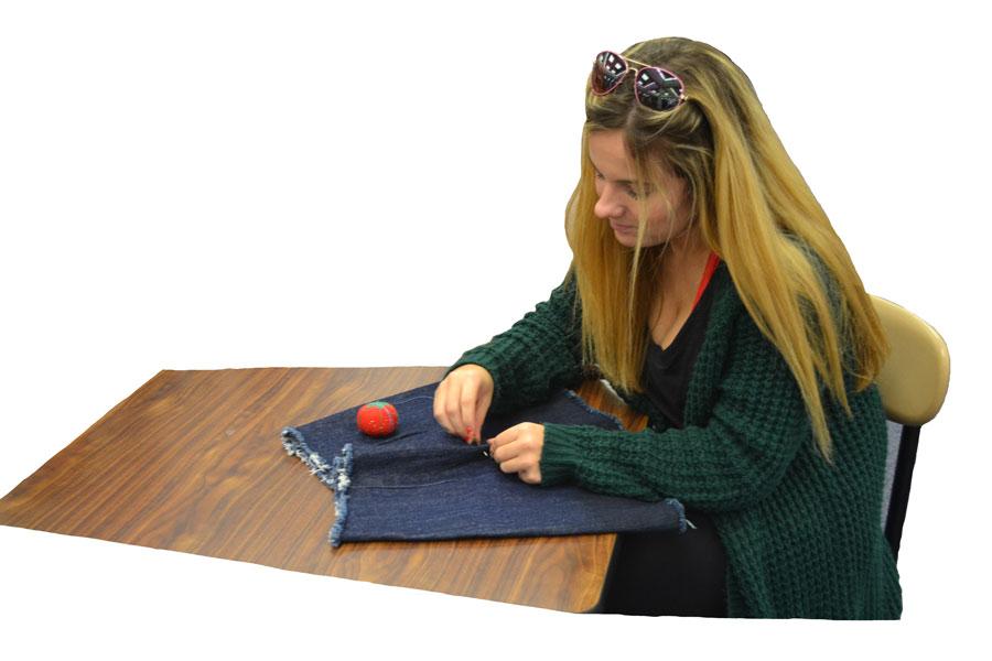 Ellie Richards sews clothing for her new line.