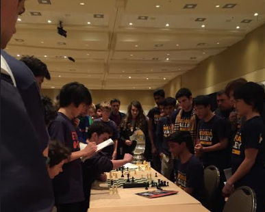 Chess team anxiously watches a match unfold