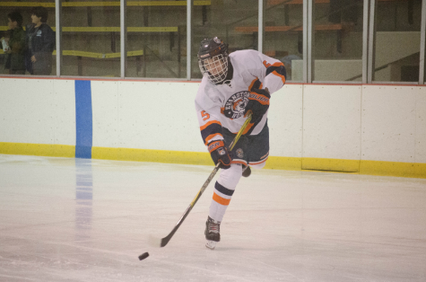Senior Fritz Gallun moves the puck across the ice.