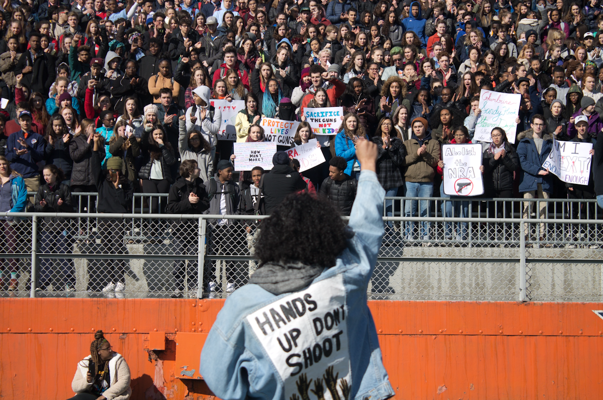 Junior Liana Wallace ends her poem about the intersection of gun violence and race by raising her fist.