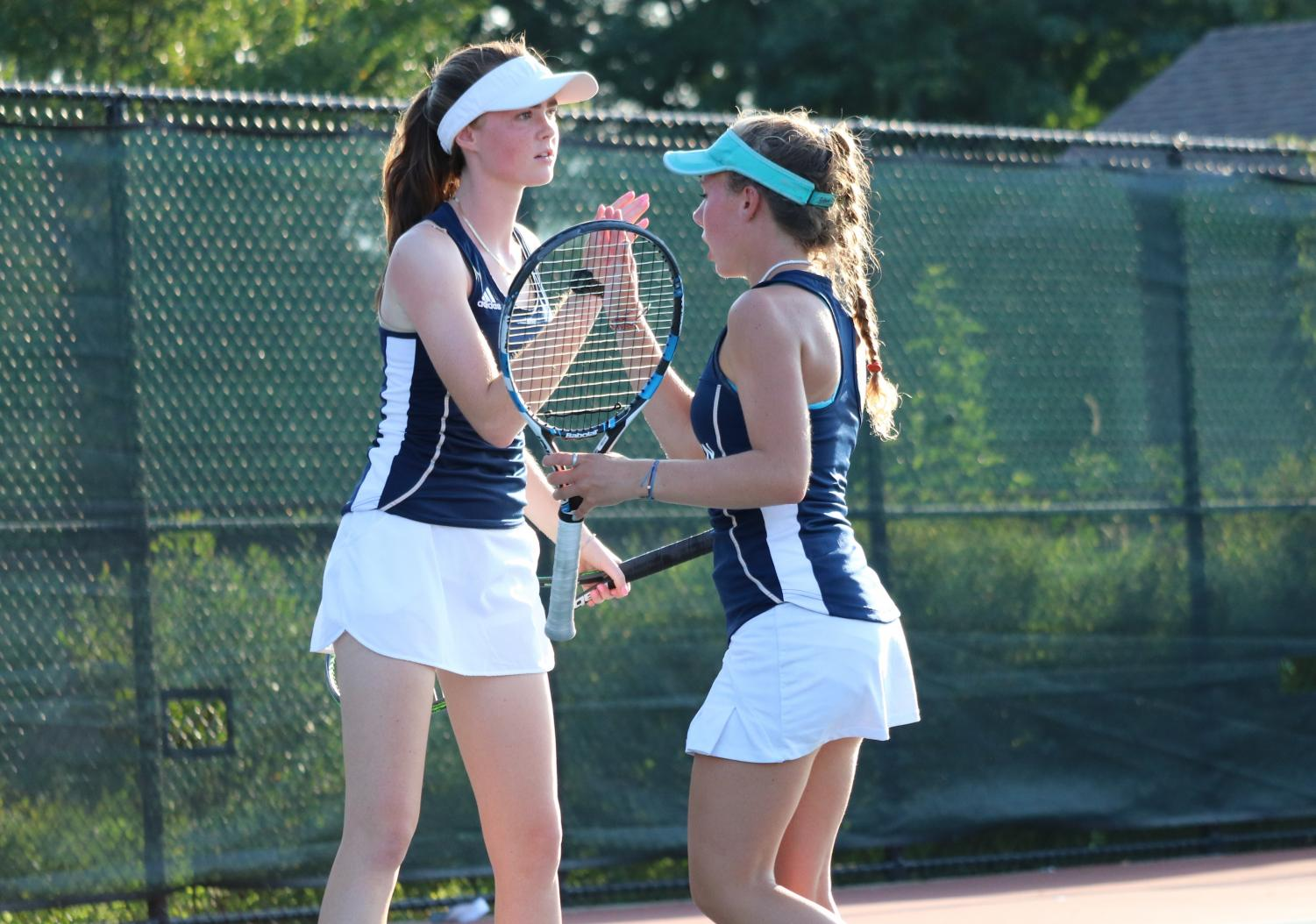 Seniors Margot Conner and Annie Hedges congratulate one another after a winning point during a regular season match versus New Trier.