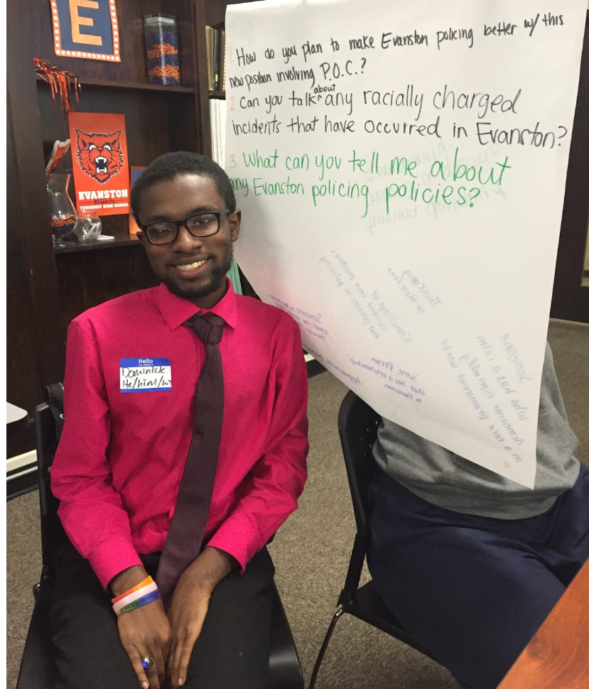 Senior Dominick Mcintosh sits next to group poster at ETHS student discussion on Oct. 16.