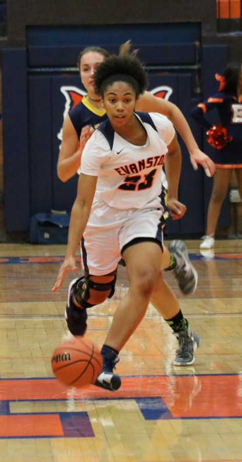 Kayla Henning, junior, dribbles down the court at Dec. 4 game against Glenbrook South. Henning recovered from an ACL injury offseason.