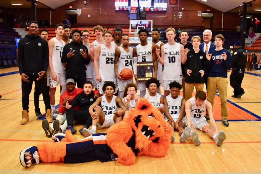 Boys basketball poses with Regional Championship trophy after Friday night win.